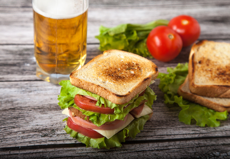 sandwich, tomato, toast, salad and glass with beer on a on a woo