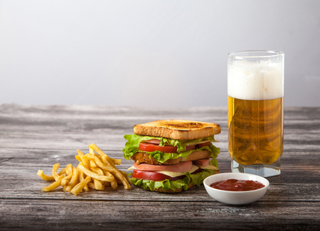sandwich with beer, fried potatoes and sauce on a wooden table Stok Fotoğraf
