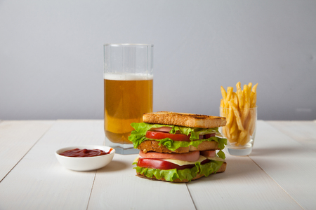 sandwich with beer, fried potatoes and sauce on a white wooden t Stok Fotoğraf