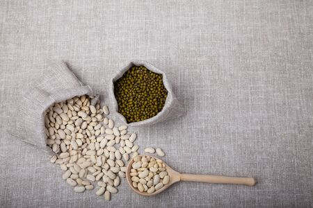 white beans spilled out of the bag, mung bean in the bag and wooden spoon lie on a linen background