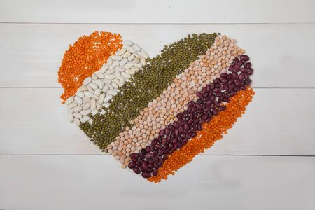 beans, lentils and beans laid out in the form of a heart on a white wooden background.