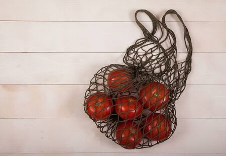 red ripe tomatoes lie in a hemp fiber net on a white wooden background.