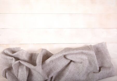 Gray cotton napkin lies on a white wooden background. Horizontally. Copy cpaes. Reklamní fotografie