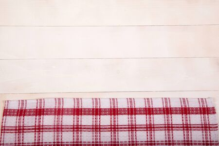 A linen tablecloth with red cells lies flat on a white wooden background. Horizontal.