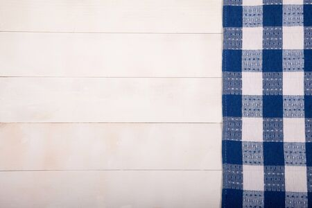A linen tablecloth with blue cells lies flat on a white wooden background. Horizontal.