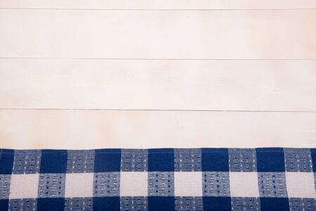 A linen napkin with blue cells lies flat on a white wooden background. Horizontal. Reklamní fotografie