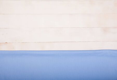 A blue cotton napkin lies flat on a white wooden background. Horizontally. Copy spaes. Reklamní fotografie