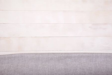 Linen light gray tablecloth lies on a white wooden background. Horizontally. View from above. Copy spaes.