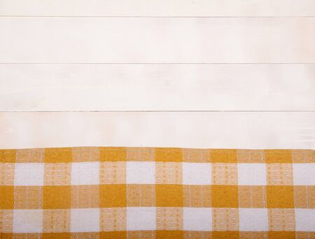 Linen yellow tablecloth lies on a white wooden background. Horizontally. View from above. Copy spaes