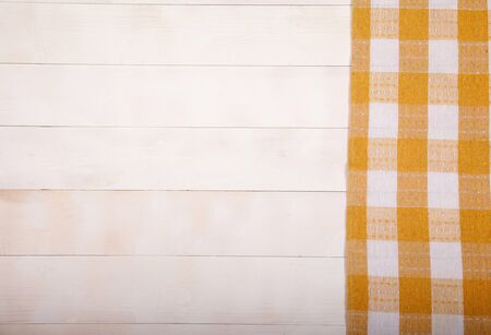 Linen yellow napkin lies on a white wooden background. Horizontally. View from above. Copy cpaes.