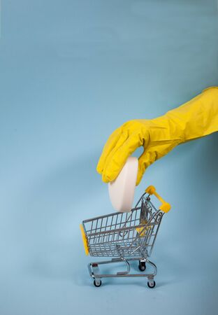 Female hand in a yellow glove dips a white bar of soap in a supermarket trolley on a blue background. Disinfection, Coronvirus. Hygiene. Virus. covid 19
