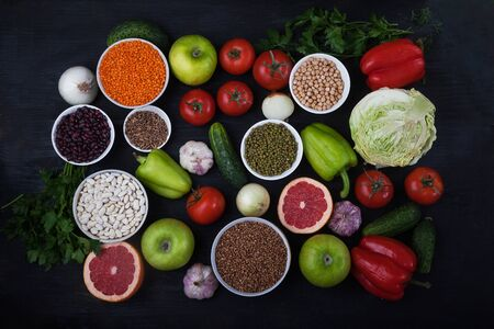 Healthy vegetarian food concept. Cereals, beans, mung bean, lentils, tomatoes, onions, garlic, parsley on a black background. Flay lay