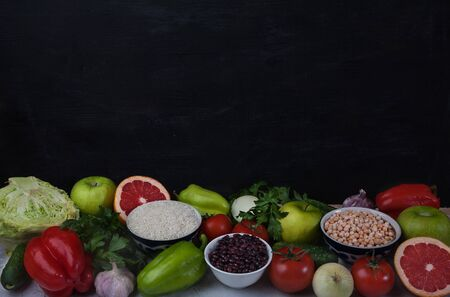 The concept of healthy vegetarian food, rice products, chickpeas, tomatoes, cucumbers, garlic and fruits on a black background. Food rich in antioxidants and vitamins. Copy spaes. Flat lay Banco de Imagens
