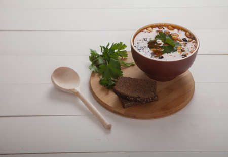 Vegetable soup with beans, olives, cheese and fresh herbs is on a wooden stand. Rye bread, wooden spoon on a white wooden table. Vegetarian cuisine