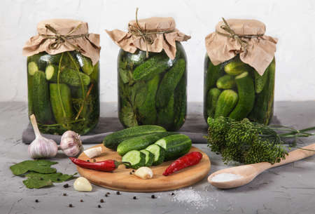 Three large glass jars with fermented cucumbers, cut cucumbers on a wooden board stand on a concrete gray background. horizontally Foto de archivo