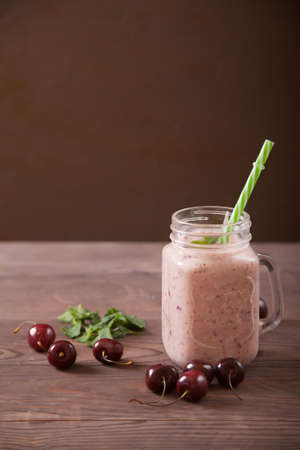 Cherry smoothies in a glass jar with straws and sprinkled cherries on a wooden table. Copy spaes.
