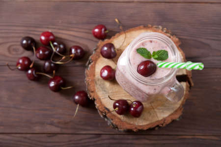 Sweet cherry smoothies in a jar with a straw, scattered berries on a wooden background. Vegetarian food. Healthy eating.