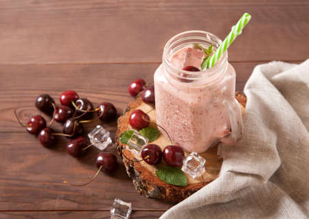 Cold refreshing sweet cherry and milk smoothie in a glass jar with straws, scattered berries and ice, linen napkin on a wooden background.
