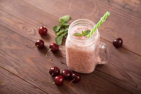 Sweet cherry smoothie in a glass jar with straws on a wooden background and scattered cherry berries nearby. View from above.
