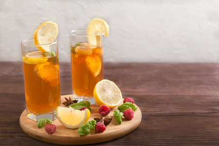 Two glasses with kombucha and lemon slices and star anise on a wooden table. Copy spaes. Horizontally Imagens