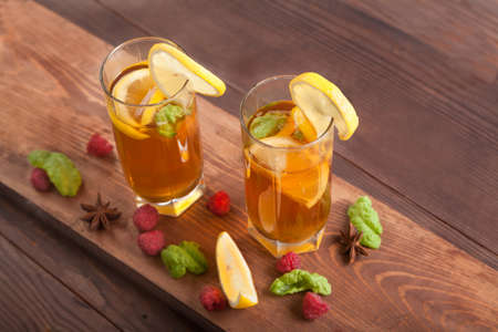 Two glasses with kombucha, drinking straws and lemon slices, raspberries are on a wooden table. Healthy food concept. Imagens