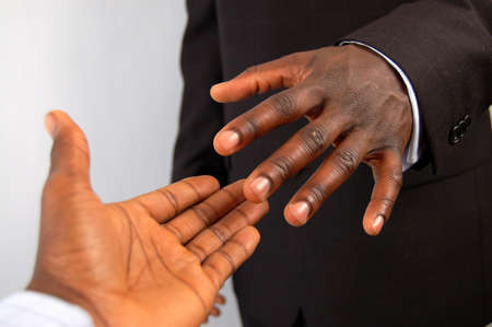 reached: This is an image of a pair of black business hands reaching out to each other, to do a handshake.