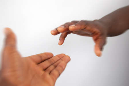 willing: This is an image of a pair of black hands reaching out to each other in motion.