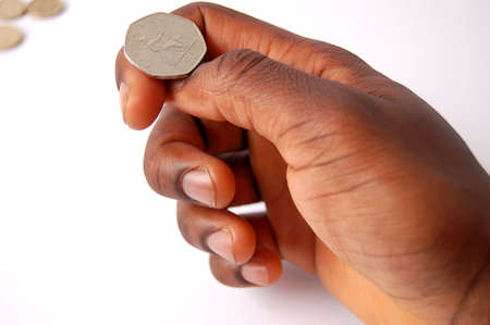 This is an image of black hand tossing a 50 pence coin. Stock Photo