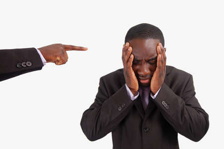 This is an image of a man feeling guilty, with a finger pointing at him. Stock Photo