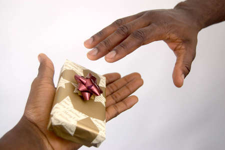 This is an image of a hand offering a christmas present, to another reaching out for it.
