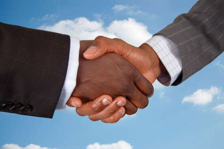 This is an image of two business hands performing a handshake, with a cloud background.
