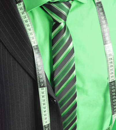 This is an image of business man wearing a tape measure across his suit and shirt.Fashion concept. Stock Photo