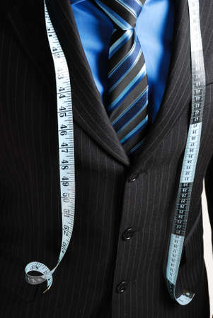 measuring: This is an image of business man wearing a tape measure across his suit.