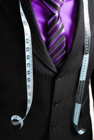 This is an image of business man wearing a tape measure across his suit and shirt.Fashion concept. photo