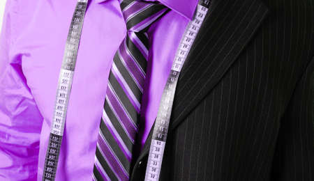 'tape measure': This is an image of business man wearing a tape measure across his suit and shirt.Fashion concept. Stock Photo