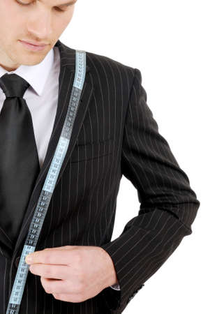 This is an image of business man using a tape measure to measure across his suit. photo