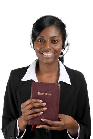 This is an image of a woman holding a bible and wearing a headset. This image can be used for christian counselling themes. Stock Photo