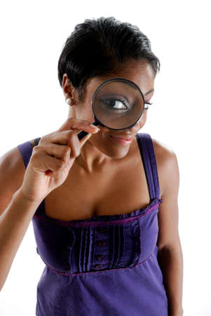 This is an image of a female student looking through a magnifying glass. photo