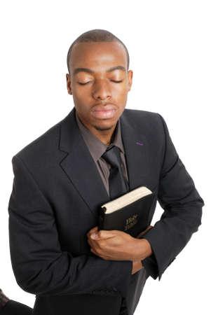 Dies ist ein Bild von ein Geschäftsmann auf die Knie eine Bibel halten.