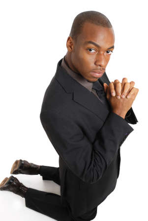 This is an image of business man kneeling doing a prayer gesture. photo