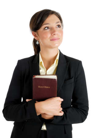 This is an image of young woman holding a bible whilst looking up.