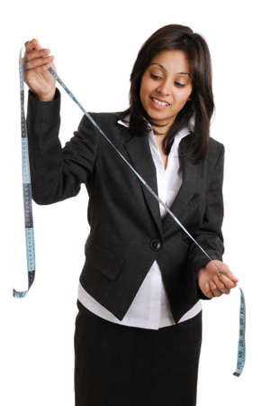 This is an image of a business woman looking at a measuring tape. Stock Photo - 9425169