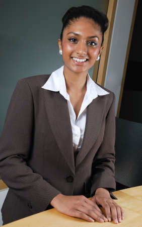 This is an image of a business woman smiling confidently at a reception desk. Stock Photo