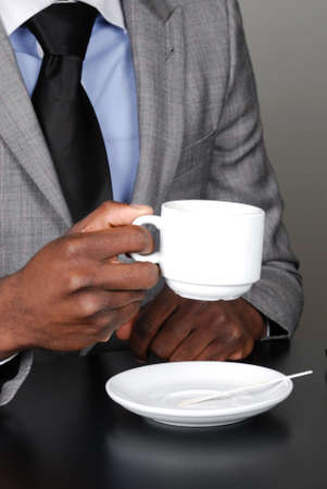 This is an image of a business man holding a cup of coffee.
