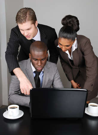 This is an image of a multi ethnic business team working on laptop.