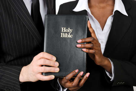 This is an image of a business couple holding a bible.