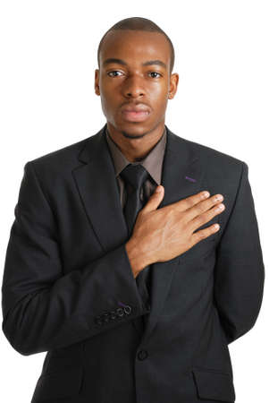 This is an image of a business man with his hand on his chest.