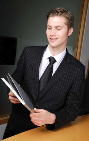 This is an image of a business man holding a book.