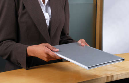 This is a image of receptionist handing over a book. Stock Photo