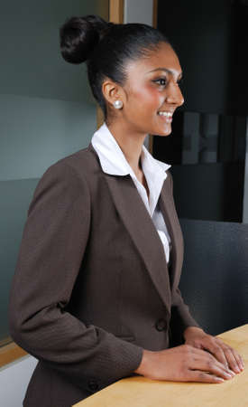 This is an image of a smiling business woman by the reception.